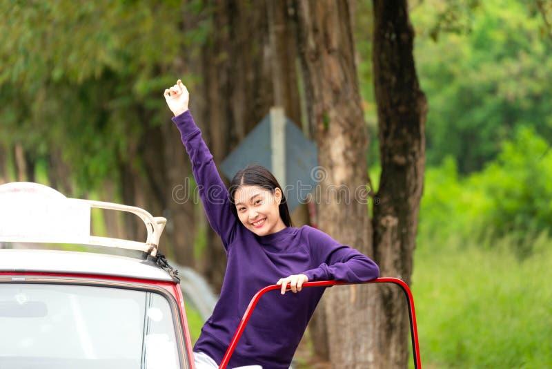 Asiatisk ung kvinna för turism i bilvägturen som ut vinkar le för fönster som är lyckligt och att koppla av i semestrarna arkivfoto