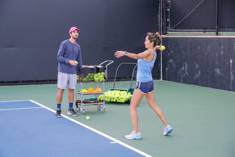 Asiatisk ung kvinna med hennes instruktör som öva utomhus- tennis royaltyfri foto