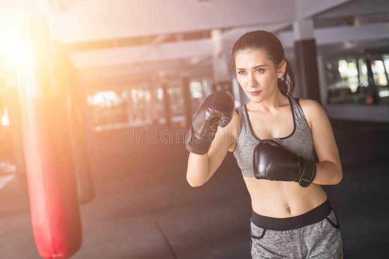 Asiatisk ung kvinna som gör övning med thailändsk boxas Muay thailändsk eq royaltyfri bild