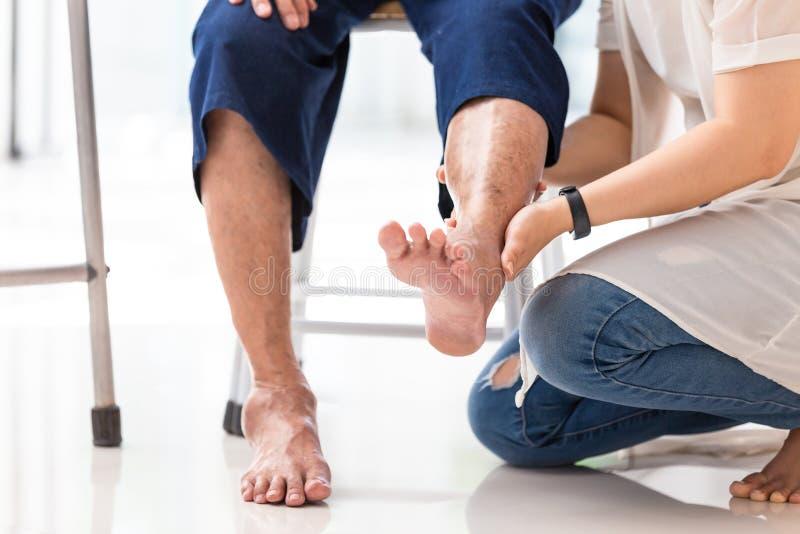Asiatisk ung kvinna som hemma kontrollerar knäet av den äldre kvinnan, hög kvinna som mottar massage av den kvinnliga physicterap fotografering för bildbyråer
