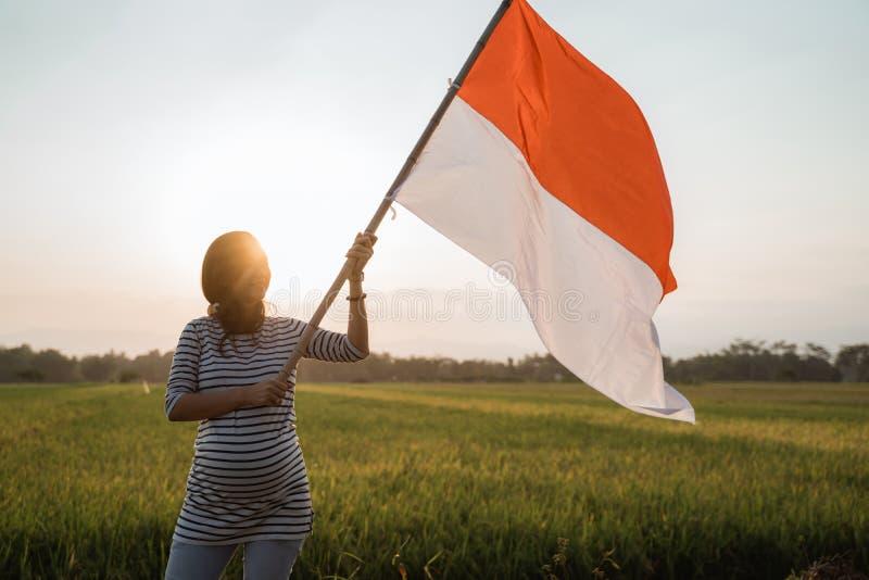 Asiatisk ung kvinna som viftar med den indonesiska flaggan arkivbilder