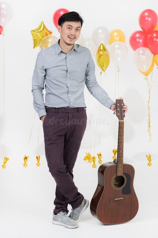 Asiatisk ung man med gitarren arkivfoto