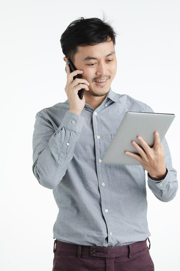 Asiatisk ung man som använder minnestavlan och smartphonen royaltyfri fotografi