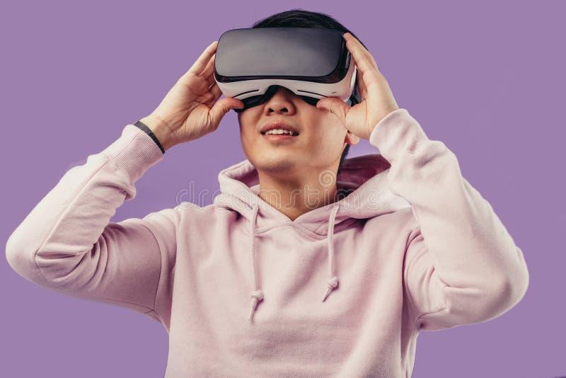 Asiatisk ung man som använder virtuell verklighethörlurar med mikrofon som isoleras över violett bakgrund arkivbilder