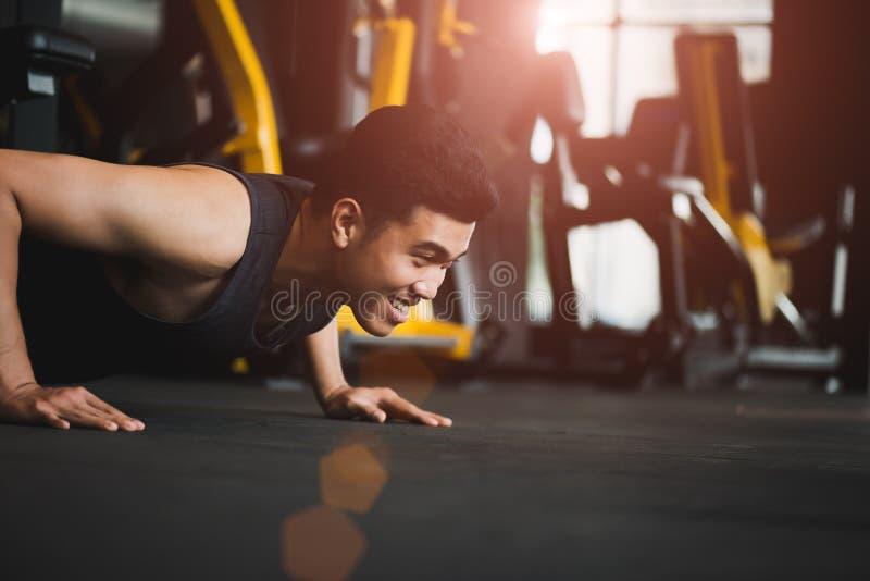 Asiatisk ung man som gör skjuta-UPS på idrottshallen Muskulöst kvinnligt göra arkivbild