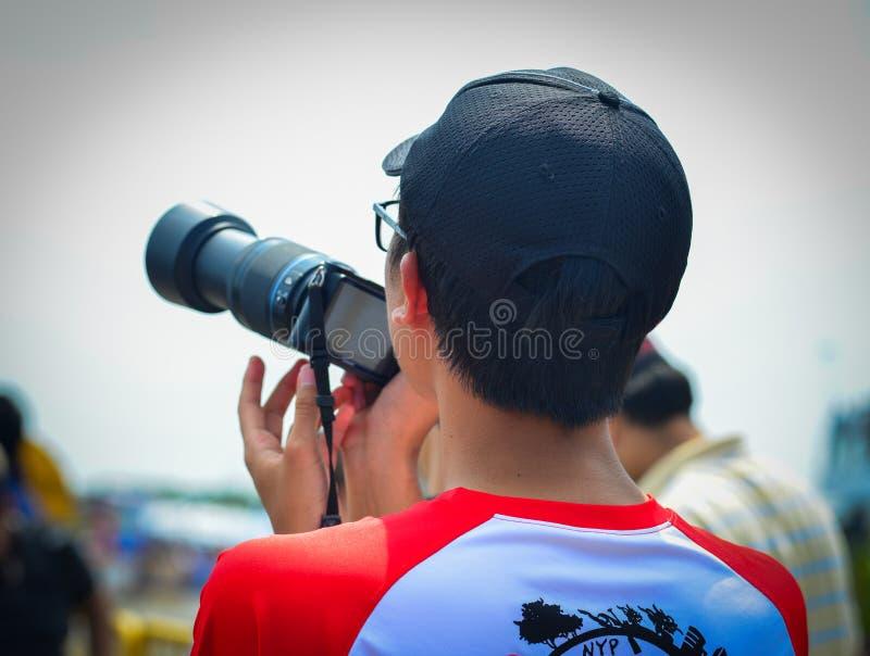 Asiatisk ung man som håller ögonen på plan show royaltyfri bild
