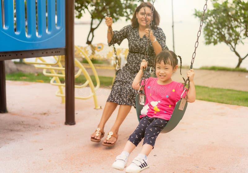 Asiatisk ung moderlek på en gunga med hennes förtjusande lilla dotter på parkerar, mamman och har lite roligt och lyckligt royaltyfria bilder