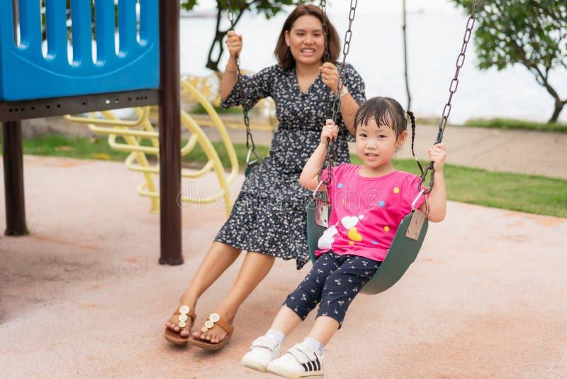 Asiatisk ung moderlek på en gunga med hennes förtjusande lilla dotter på parkerar, mamman och har lite roligt och lyckligt arkivfoton