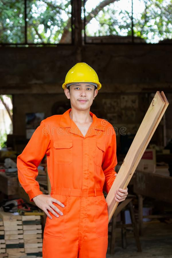 Asiatisk ung snickare som rymmer träplankor i en fabrik royaltyfri foto