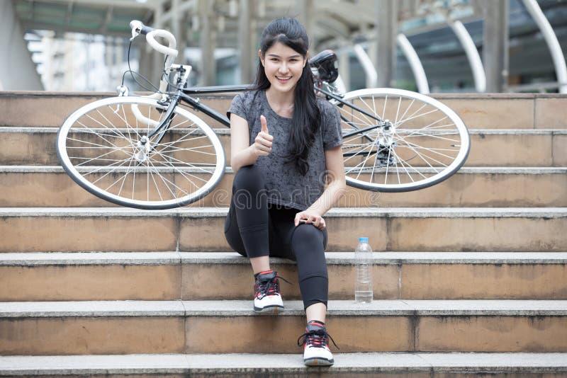asiatisk ung sportkvinna i sportswearen som sitter på trappan med cykeln och visar upp tummar att ta för flicka vilar och att kop royaltyfria foton
