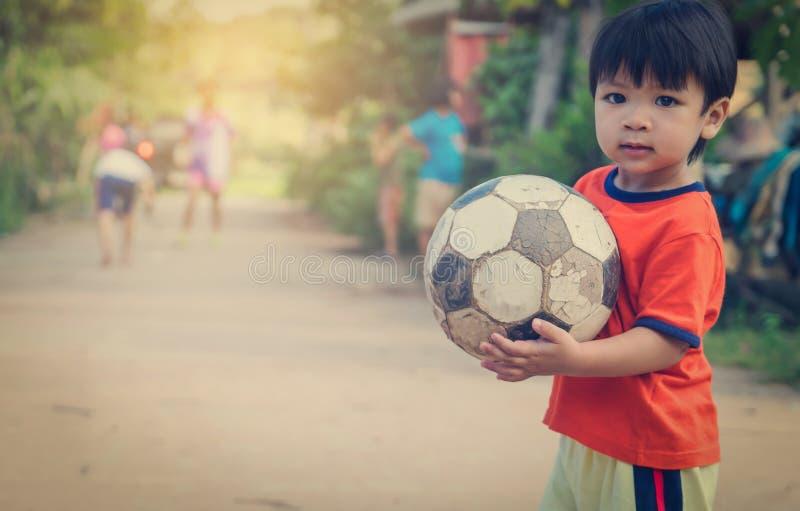 Asiatisk unge i den fattiga byn som spelar med fotbollbollen fotografering för bildbyråer