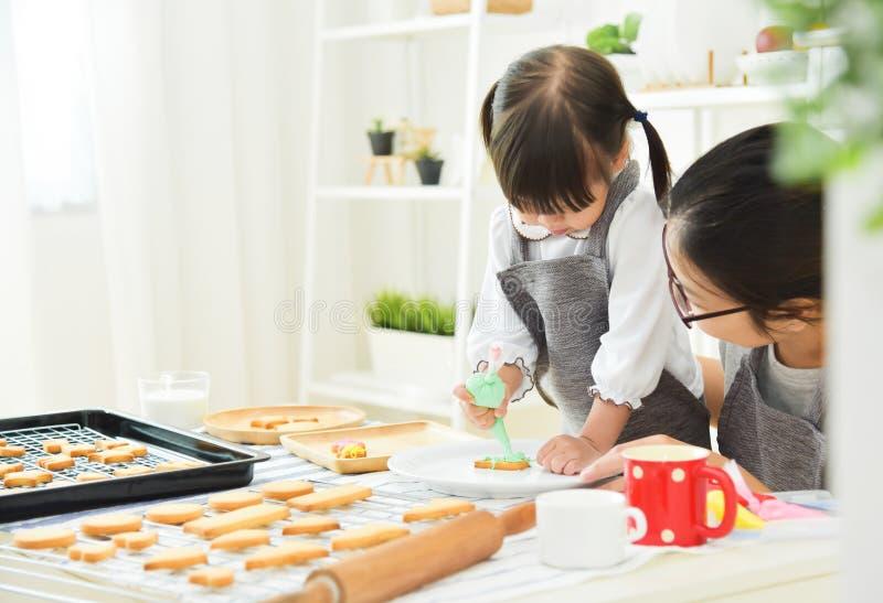 Asiatisk unge och barnmoder som dekorerar kakan arkivbilder