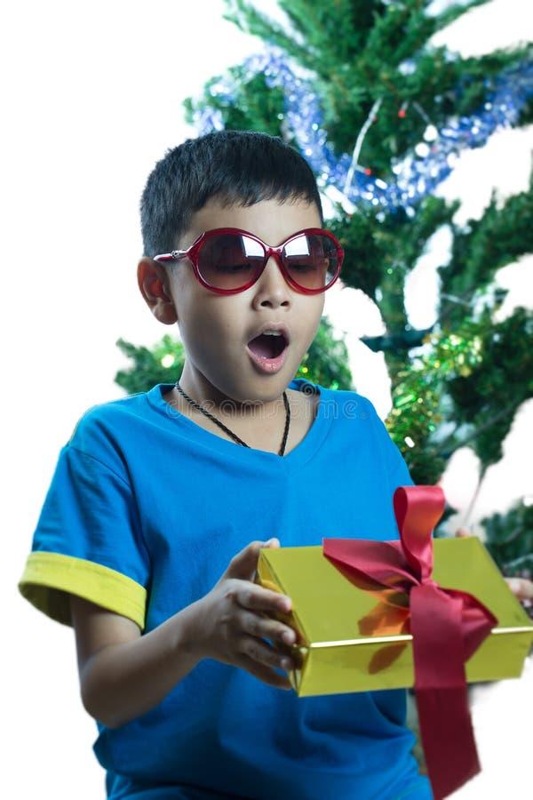 Asiatisk unge på solglasögonöverraskningen som får julklapp arkivfoton