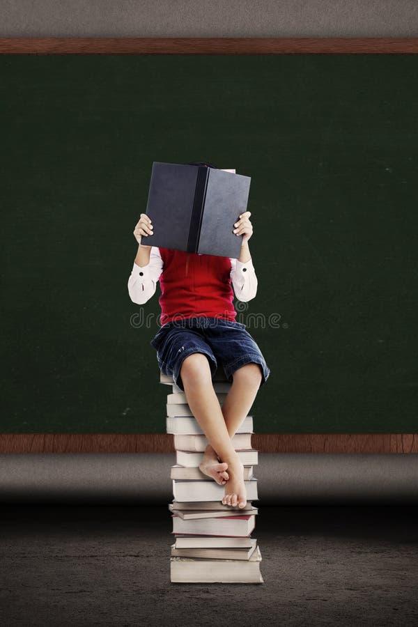 Asiatisk unge som läser en bok på bunt av böcker royaltyfri foto