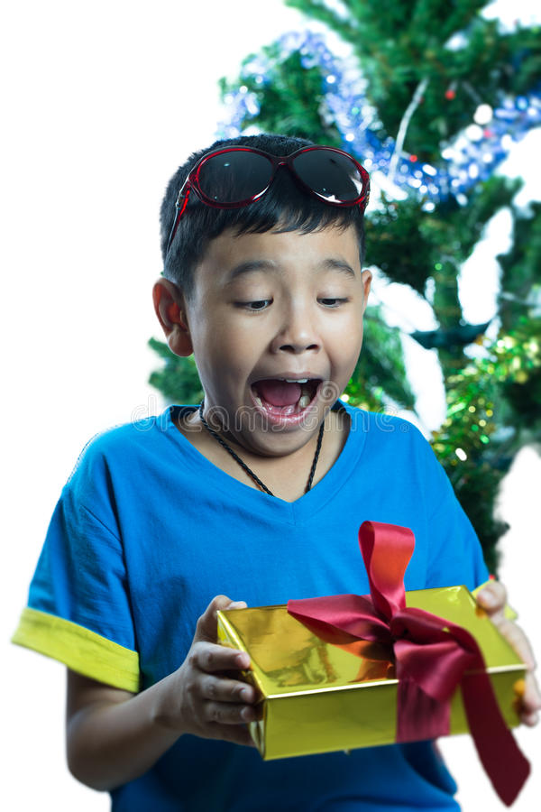 Asiatisk unge som upphetsar för att få hans julklapp royaltyfri bild