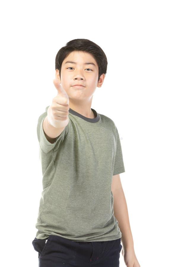 Asiatisk upphetsad pojke i gr?splan-skjortan som ger tummar-upp royaltyfria foton