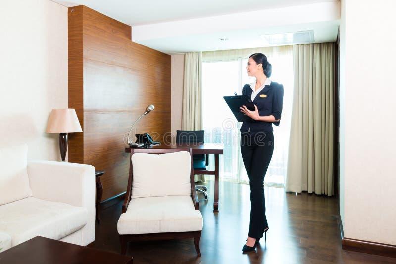 Asiatisk utövande hushållerska som kontrollerar hotellrum royaltyfri bild