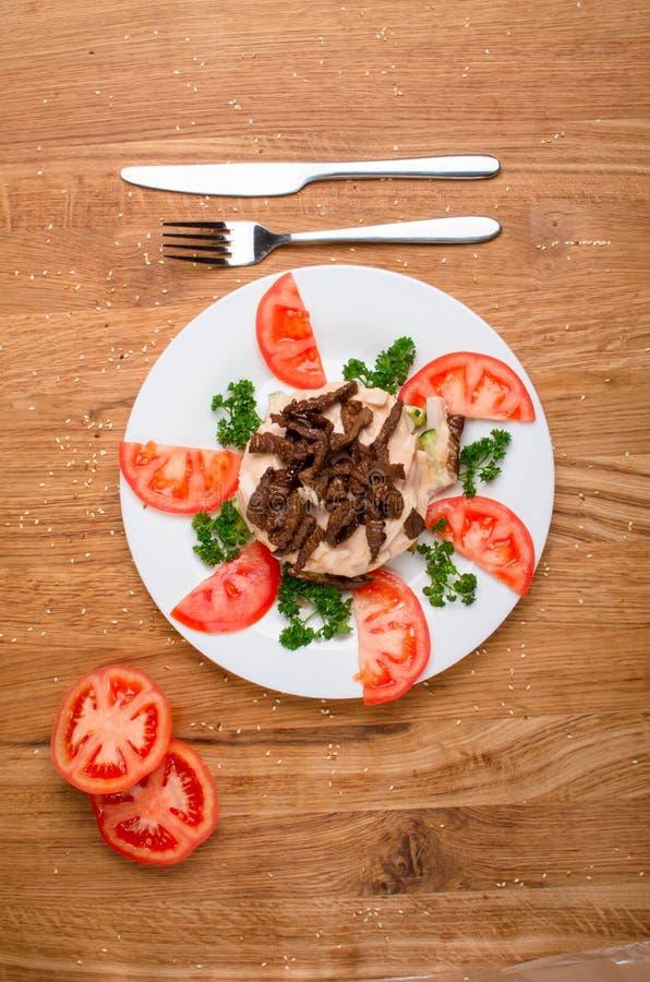 Asiatisk varm kalvk?ttsallad med gr?nsallat och tomater H?rlig restaurangmatr?tt smaklig matst?lle royaltyfria bilder