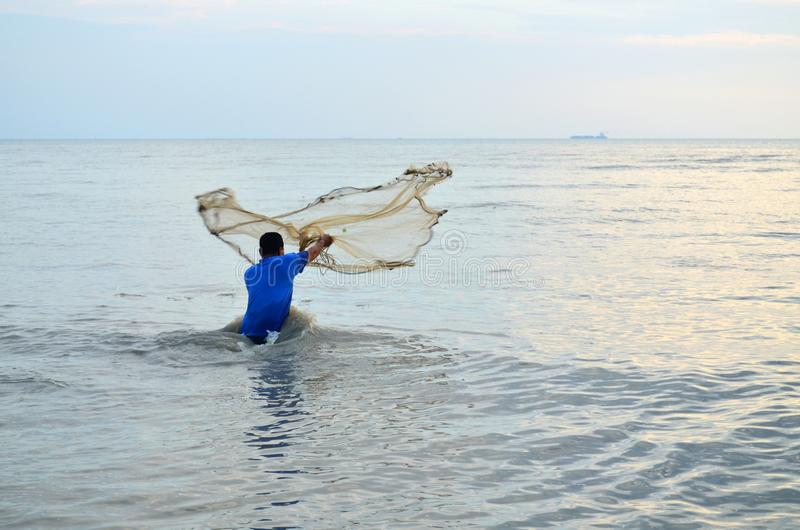 Asiatisk vuxen man som netto kastar fisken till låsfisken arkivbilder