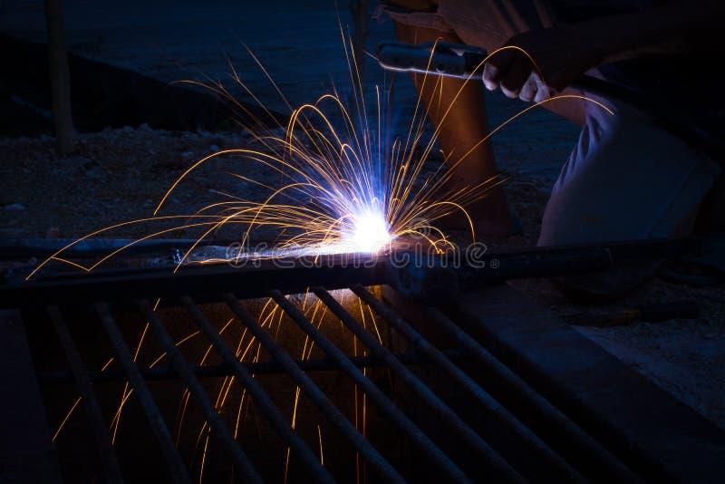 Asiatisk welderman f?r n?rbild som arbetar p? metallskulpturen p? konstruktionsplatsen royaltyfria bilder
