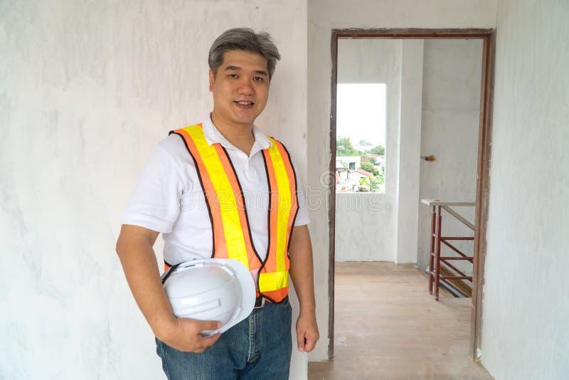 Asiatisk yrkesmässig tekniker som arbetar i huskonstruktionsplatsen för kontroll av stugan under konstruktion royaltyfria foton