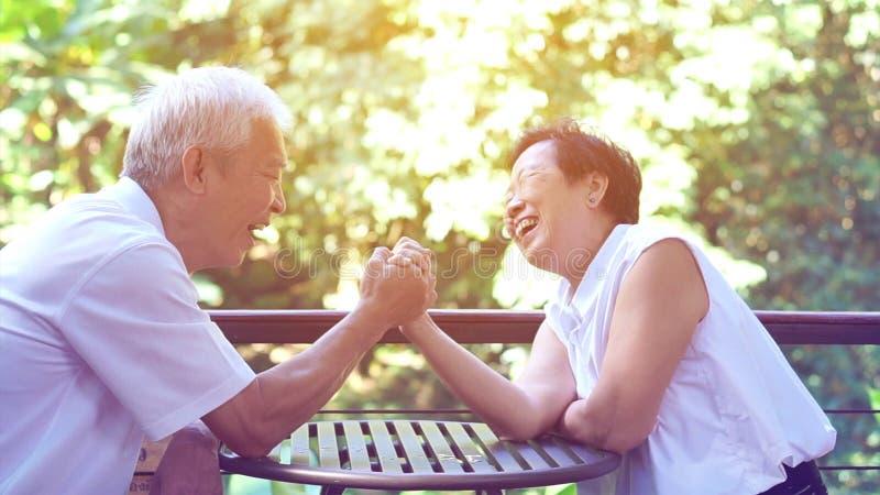 Asiatiska äldre gamla par som kompromissar i förbindelselivhemlighet av hållbar förälskelse royaltyfria foton
