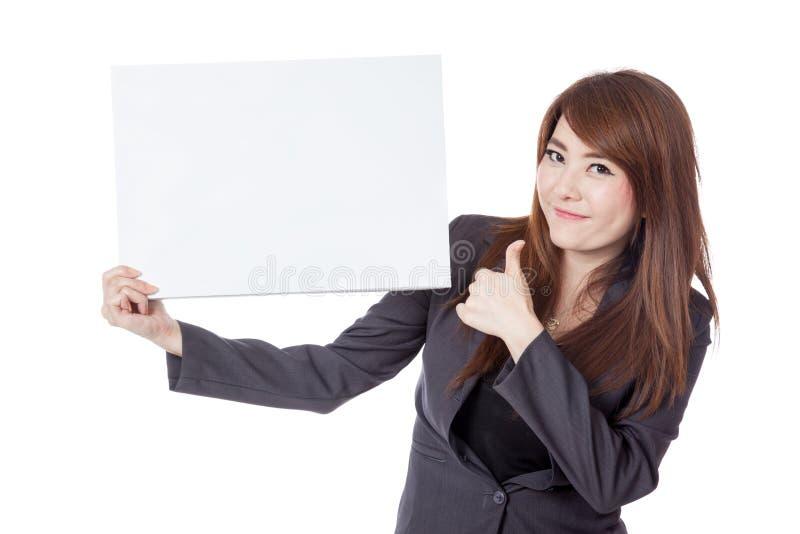 Asiatiska affärskvinnatummar-upp med ett tomt tecken royaltyfri foto