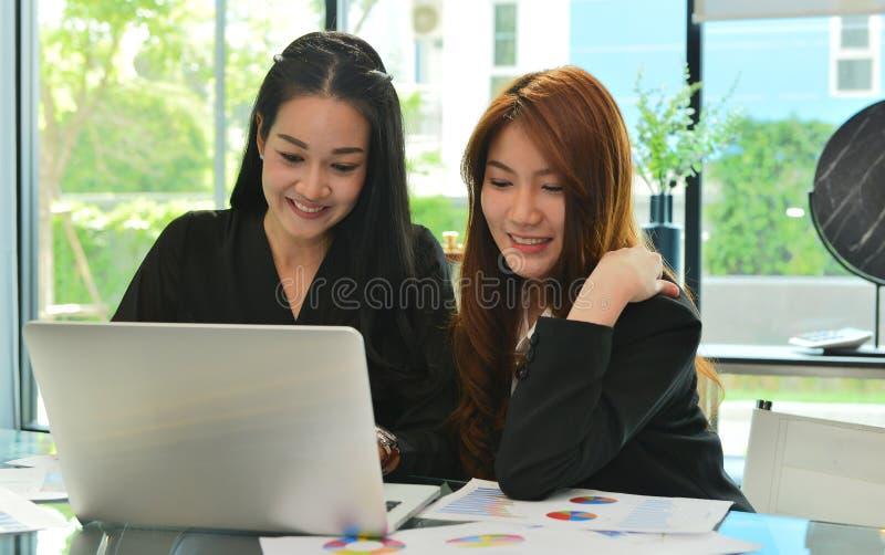 Asiatiska affärskvinnor som arbetar och använder bärbara datorn i mötesrum arkivfoton
