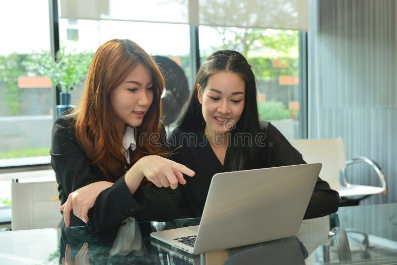 Asiatiska affärskvinnor som arbetar och använder bärbara datorn i mötesrum fotografering för bildbyråer