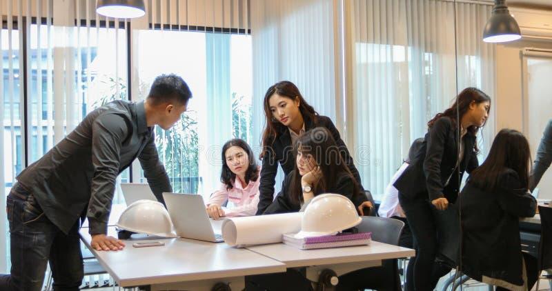Asiatiska affärsmän och grupp som använder anteckningsboken för affärspartners arkivfoto