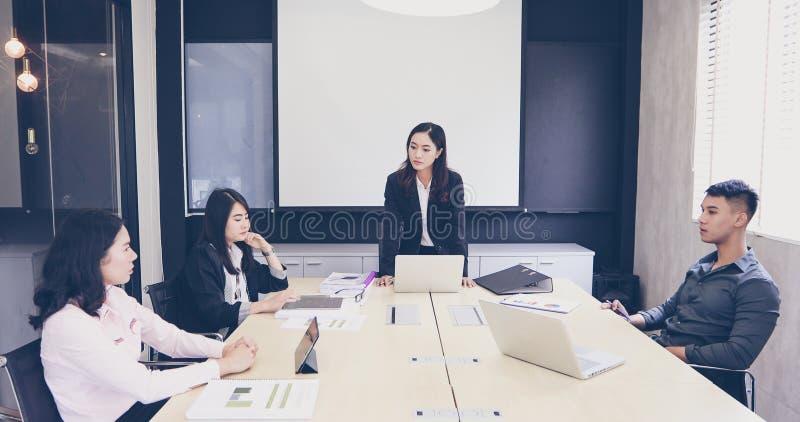 Asiatiska affärsmän och grupp som använder anteckningsboken för möte av allvarligt a arkivbilder