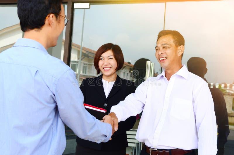 Asiatiska affärsmän som skakar händer arkivbild