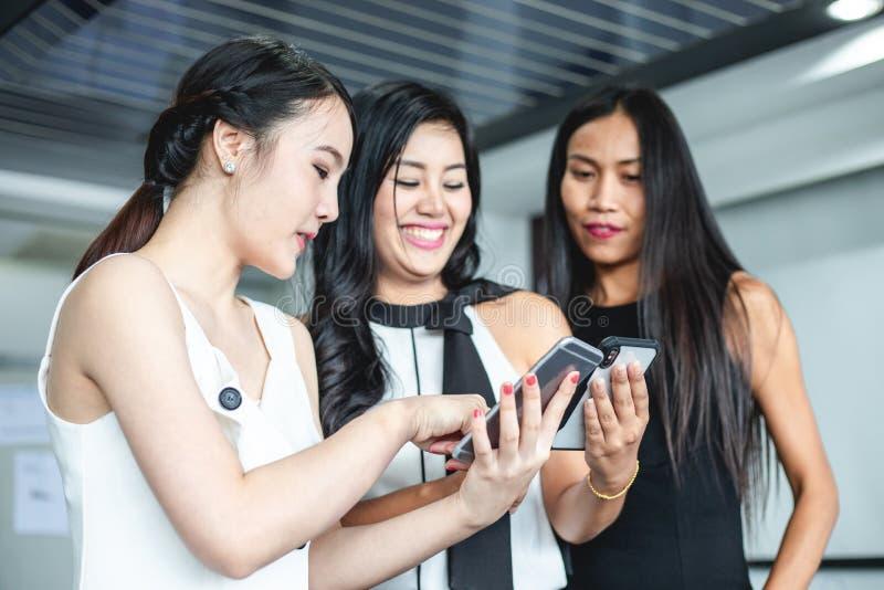 Asiatiska aff?rskvinnor med partnern diskuterar om detaljen av arbete p? att le f?r smartphone och f?r aff?rskvinnor fotografering för bildbyråer