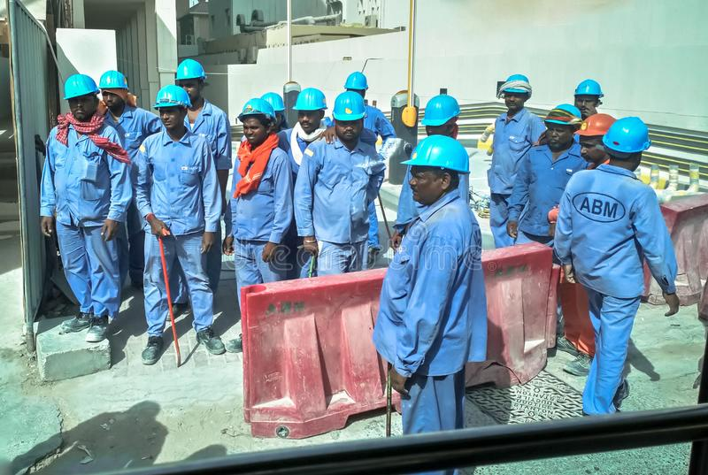 Asiatiska arbetare i Dubai En grupp av asiatiska arbetare på konstruktionsplatsen Dubai Augusti 2018 royaltyfri foto