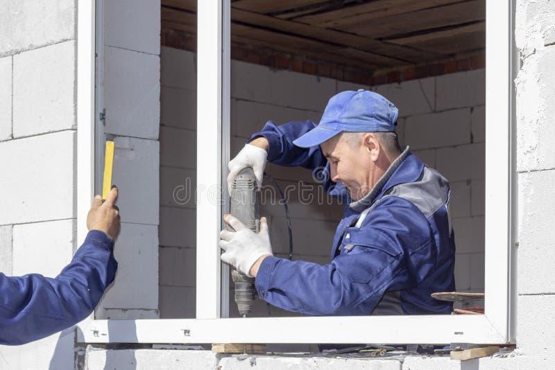Asiatiska arbetare installerar fönster till huset arkivbild