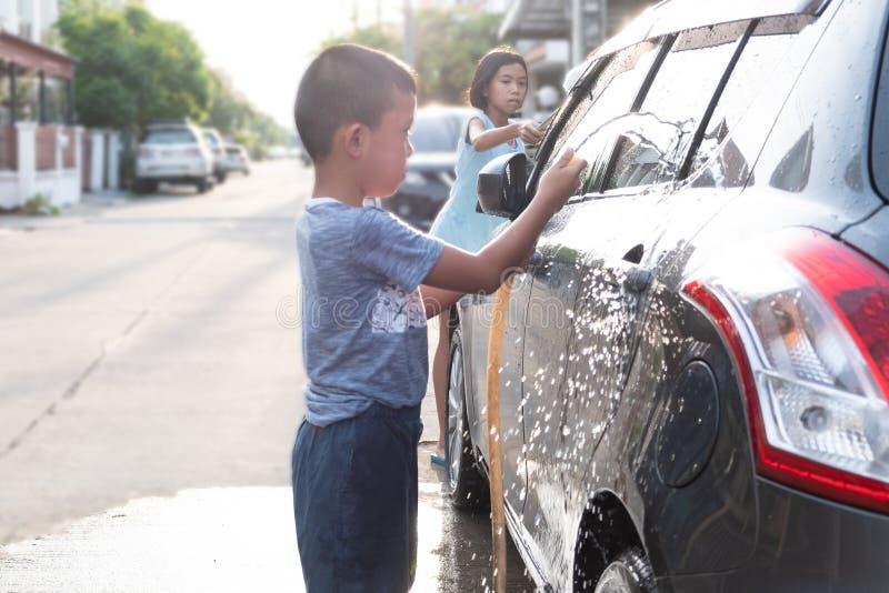 Asiatiska barn använder vattenslangen till den tvättande bilen royaltyfri foto