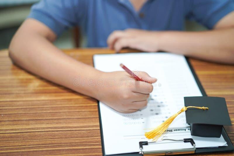 Asiatiska barn lurar för att skriva svar i en studie för frågesportundersökningsprov lär med avläggande av examenmellanrumshatten arkivfoton