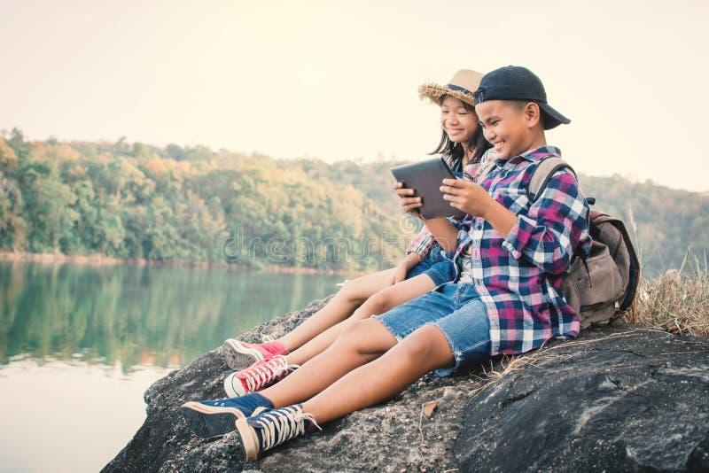Asiatiska barn som spelar minnestavlan i natur arkivbild