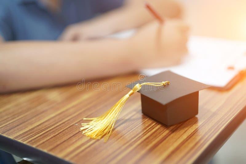 Asiatiska barn som ungen skriver svar i en studie för frågesportundersökningsprov, lär med avläggande av examenmellanrumshatten p royaltyfri fotografi