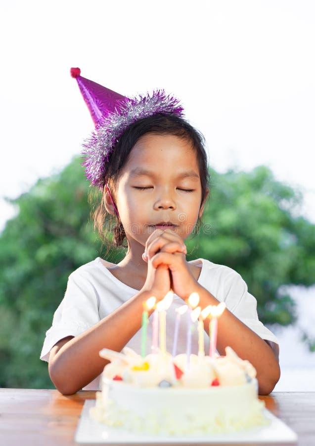 Asiatiska barnflickor gör den vikta handen för att önska den bra saker för hennes födelsedag i födelsedagparti royaltyfria bilder