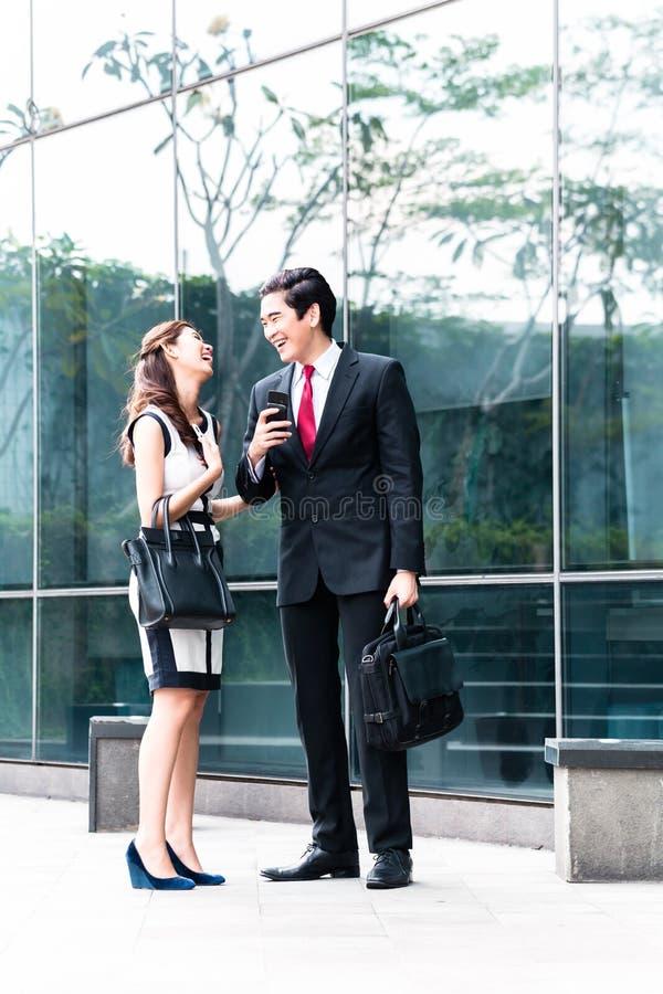 Asiatiska businesspeople som utanför talar till mobiltelefoner arkivfoto