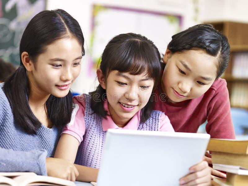 Asiatiska elementära skolflickor som använder minnestavlan i klassrum arkivbilder