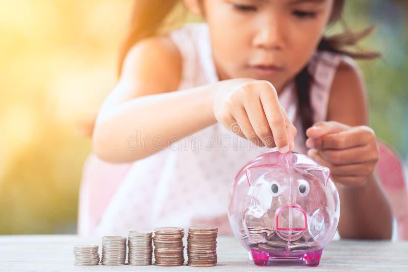 Asiatiska flickadanandebuntar av mynt och sättapengar in i spargrisen royaltyfri bild