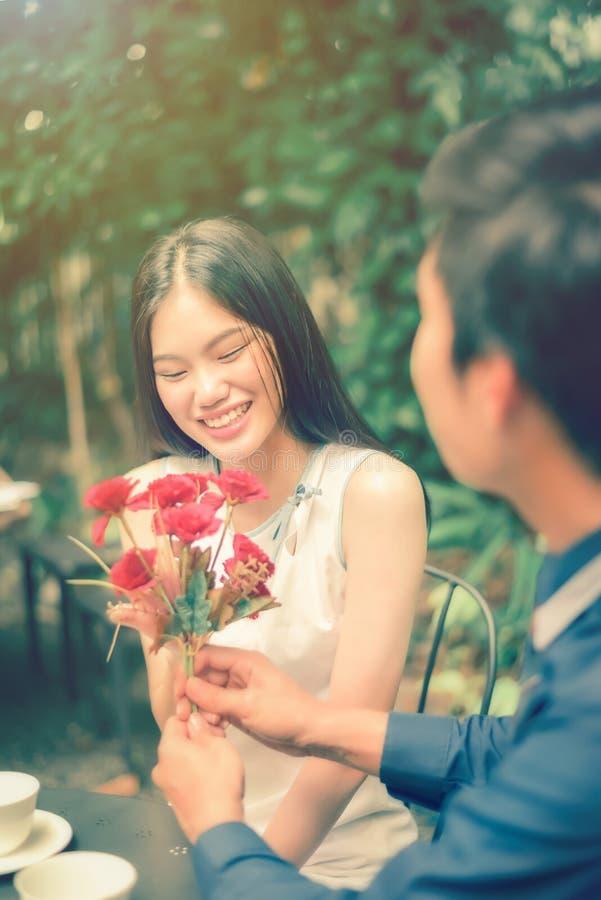 Asiatiska flickor är förtjusta de röda blommorna som mottas från fotografering för bildbyråer