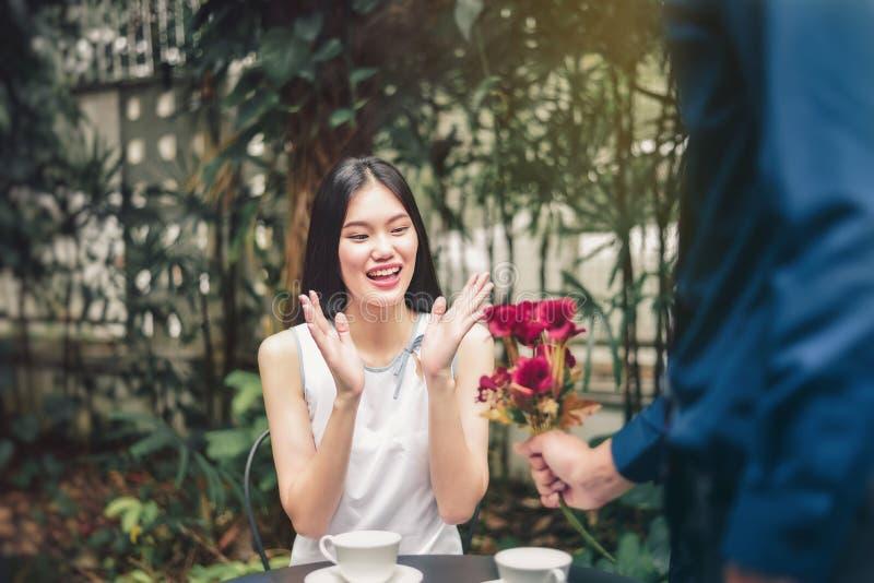 Asiatiska flickor är förtjusta de röda blommorna som mottas från arkivbild