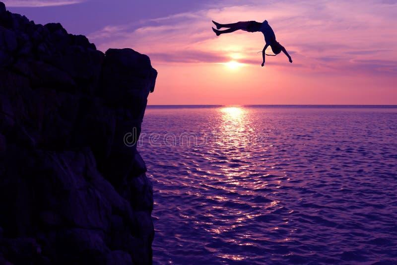 Asiatiska flickor hoppar från en klippa in i havsepisodsolnedgången, slår en kullerbytta till havet arkivbild