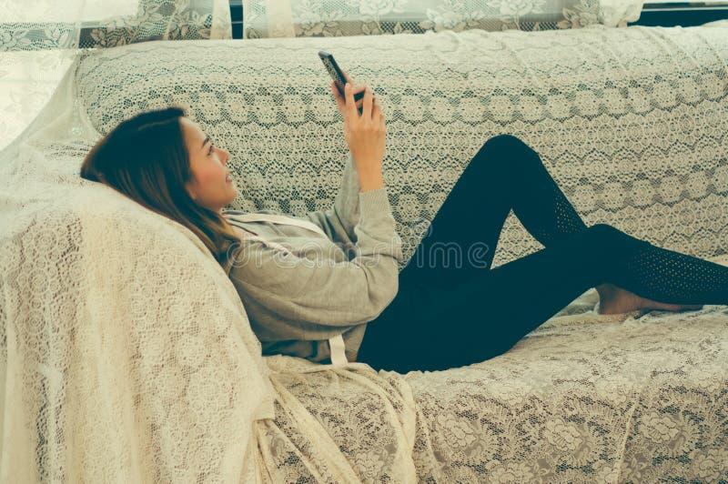 Asiatiska flickor räcker innehavsmartphonen och att le lyckligt på soffan i huset med avkoppling, begrepp av att använda teknolog royaltyfria foton