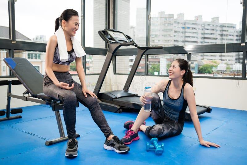 Asiatiska flickor som sitter och pratar i idrottshallen arkivbilder