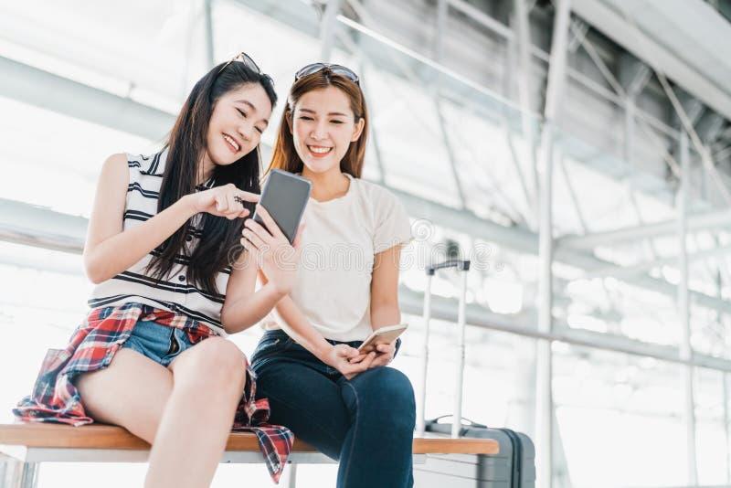 Asiatiska flickor som tillsammans använder kontrollerande flyg för smartphone eller online-incheckningen på flygplatsen, med baga arkivfoto