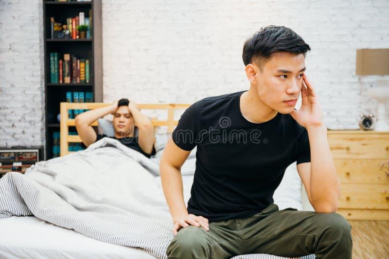 Asiatiska glade par som har argument med de i sovrum Fundersam bög som har spänning, medan annat sover royaltyfria foton